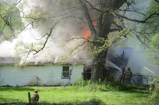 Fire engulfs a single story home at 300 Pony Ave. on Sunday.  Trace Christenson/The Enquirer