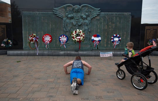 Brent Hill, 36, of Midland, who served in the Marine Corps, does 22 pushups as his son Noah, 3, looks on at right at the Midland Veterans Memorial on Memorial Day, May 25, 2020. Hill does this every day to not just honor those who serve but to shed light on those who return and commit suicide.