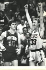 Larry Bird celebrates the win in Game 5, as Bill Laimbeer looks on, May 26, 1987 at the Boston Garden.