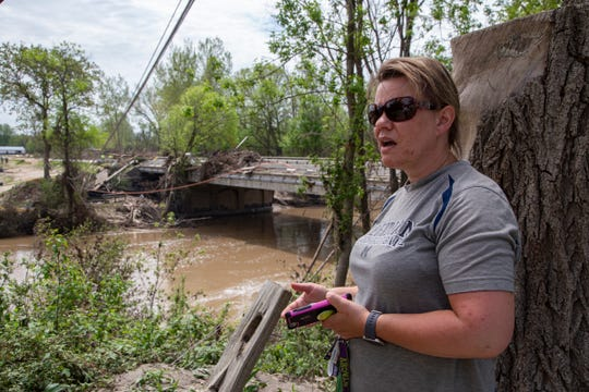Stacey Crowder, 44, of Sanford looks over the Tittabawassee River at the Saginaw Rd. Bridge on Memorial Day, May 25, 2020. Floodwaters have devastated communities like Midland and Sanford following the failure of two dams that flooded homes along the Tittabawassee River. Crowder, who lives less than a mile from the flood site still does not have power.