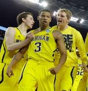 Trey Burke makes a deep 3-pointer for force overtime in an NCAA Tournament regional game against Kansas in 2013. Michigan would go on to win in OT and eventually play in the NCAA championship game.