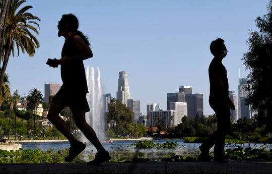 People walk at Echo Park Lake as downtown Los Angeles is seen in the background in Los Angeles. California Gov. Gavin Newsom has approved 45 of California's 58 counties to reopen some businesses since May 8 when he loosened his original mid-March stay-at-home order.