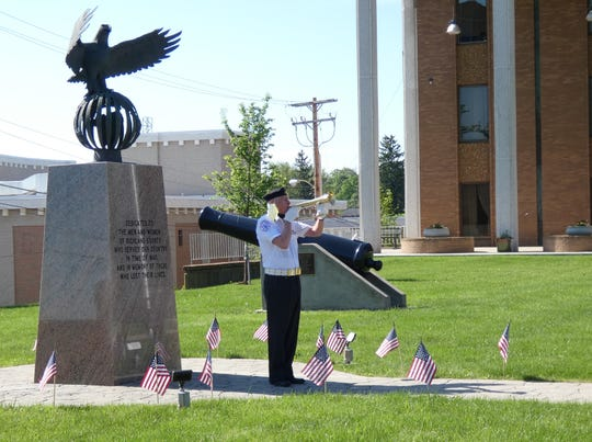 """Korean War veteran Bill Miller plays """"Taps"""" during the Joint Veteran Burial Squad's short Memorial Day service Monday morning in front of the Richland County Courthouse."""
