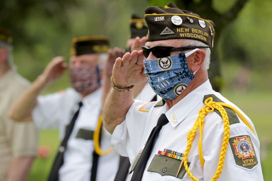 Navy veteran Richard Taczala of New Berlin, a Vietnam-era veteran with VFW Post 5716 in New Berlin, salutes as taps is sounded during a Memorial Day community drive-by ceremony at Highland Memorial Park Cemetery in New Berlin on Monday. VFW Post 5716 conducted its annual Memorial Day ceremony but  required all attending to remain in their vehicles as they drove by the memorial in single file to pay tribute to fallen military service members.