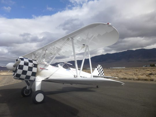 This WWII-era white and checkerboard open-cockpit biplane will fly over senior living communities to honor veterans on May 25.