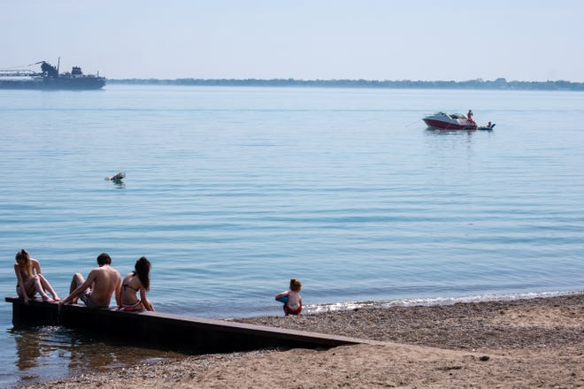 A boat floats on Lake Huron near a small group of people playing at Lakeside Beach on Memorial Day, Monday, May 25, 2020, in Port Huron. The coronavirus pandemic and social distancing rules didn't deter a crowd from forming on the beach.