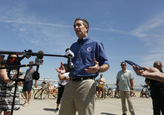 In this Saturday, May 23, 2020, photo, Gov. Ralph Northam talks to the media during a brief visit to the Oceanfront in Virginia Beach, Va., to see for himself how crowded the beach was. Northam has repeatedly urged Virginia residents to cover their faces in public during the COVID-19 pandemic, but the Democrat didn't heed his own plea when he posed mask-less for photographs alongside residents during the weekend beach visit. A spokeswoman for the governor's office said on Sunday that Northam should have brought a face mask with him during his visit on Saturday to the Virginia Beach Oceanfront.