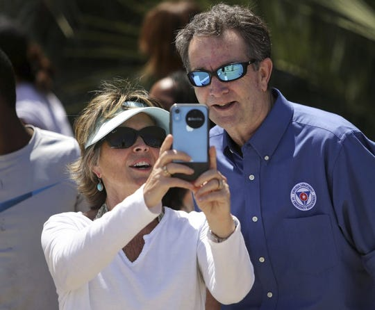 In this Saturday, May 23, 2020, photo, Gov. Ralph Northam and Tori Bloxom, of Onancock, Va., take a selfie as the governor visits the Oceanfront in Virginia Beach, Va., to see for himself how crowded the beach was. Northam has repeatedly urged Virginia residents to cover their faces in public during the COVID-19 pandemic, but the Democrat didn't heed his own plea when he posed mask-less for photographs alongside residents during the weekend beach visit. A spokeswoman for the governor's office said on Sunday that Northam should have brought a face mask with him during his visit on Saturday to the Virginia Beach Oceanfront.