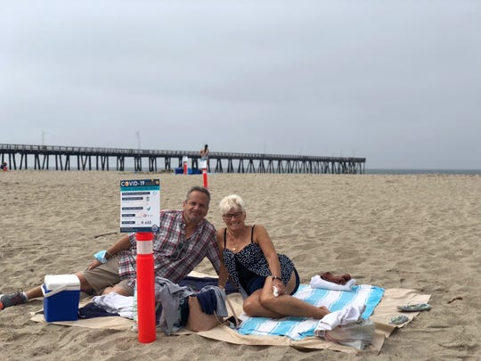 Rick Cosendino and Cathy Gerhardt of Chatsworth lounge at Port Hueneme beach on Monday, May 25, 2020. The couple were happy with the cones placed on the beach used to ensure beachgoers maintained social distancing.