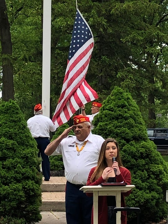 Vineland High School senior Alexandra Brodzik performs the National Anthem while Edwin Alicea, the United Veterans Council President, salutes during a Memorial Day observance in Landis Park in Vineland. May 25, 2020