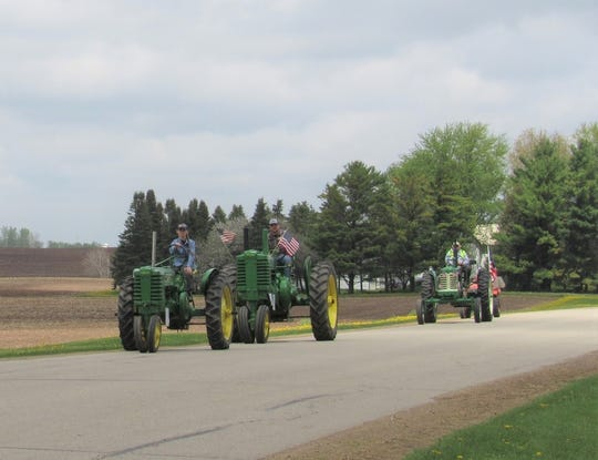 The stars and stripes lends a patriotic feel to these John Deere tractors that were a part of the impromptu tractor parade on the rural byways of Seymour, Wis.