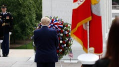 President Donald Trump stands before a wreath at the Tomb of the Unknown Soldier in Arlington National Cemetery.