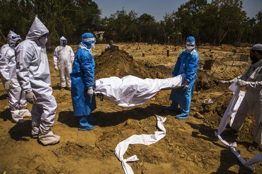 Indian health workers in hazmat suits bury a 55-year-old Muslim who died from the coronavirus, during Eid ul-Fitr, the Muslim festival marking the end of the holy fasting month of Ramadan, on May 25, 2020 in Delhi, India. Eid-ul-Fitr, considered one of the most important festivals in Islam, lacked its traditional fervor as religious gatherings remain banned in India as the country reels under a lockdown imposed by the government on March 25 to prevent the spread of coronavirus. Over 4,000 people have died and there have been over one hundred forty thousand infections so far.