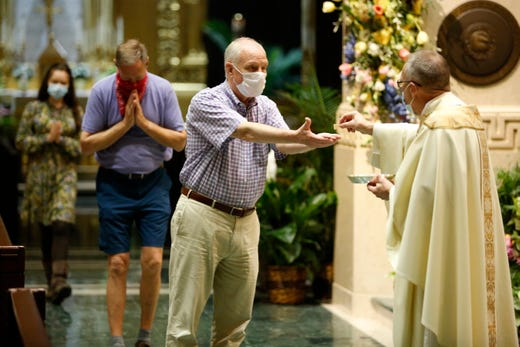 Congregation members wear face masks as they receive communion from the Rev. Jan Schmidt during a morning Mass at the Cathedral of St. Peter in Chains Catholic Church in downtown Cincinnati on May 25. The Memorial Day Mass was the first inside the church since the state-mandated stay-home order in March.