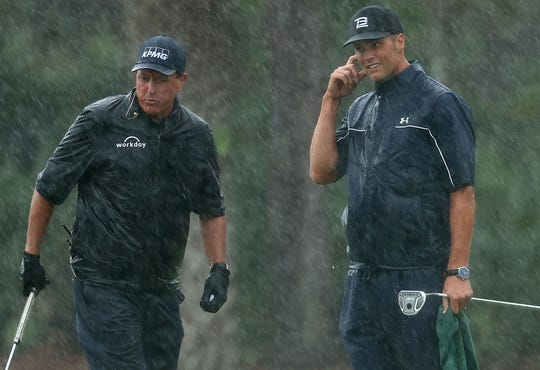 Phil Mickelson and Tom Brady react on the 13th green.