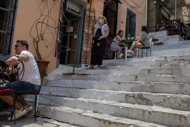 People drink coffee in Plaka district of Athens on May 25, 2020. Greece restarted regular ferry services to its islands, and cafes and restaurants were also back open for business as the country accelerated efforts to salvage tourism season.