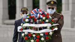 May 25, 2020; Washington, DC, USA; David Yoho, 92, who served with the U.S. Merchant Marines during World War II (left) takes part during a wreath laying ceremony at the National WWII Memorial alongside Patrick McCourt, a living history volunteer WWII re-enactor (right) on Memorial Day, Monday, May 25, 2020. Jack Gruber-USA TODAY
