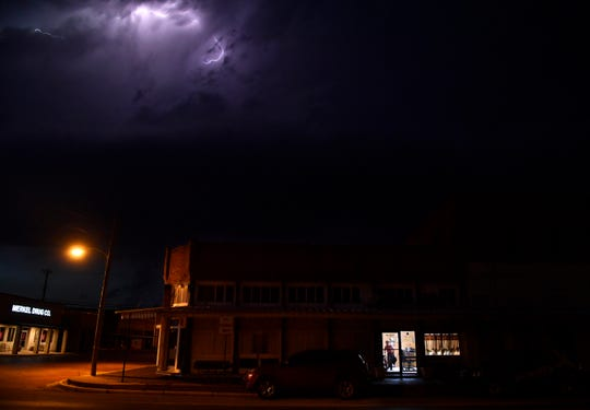 Turning out the lights at the Merkel Mail office, John Starbuck is framed in the doorway as lightning flashes in the sky overhead Thursday. After 130 years in print, Starbuck is folding the newspaper today due to losses in advertising.