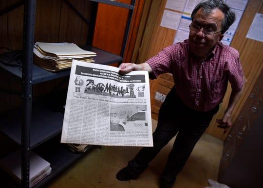 John Starbuck holds out a copy of the Merkel Mail inside the newspaper office's storeroom Thursday.