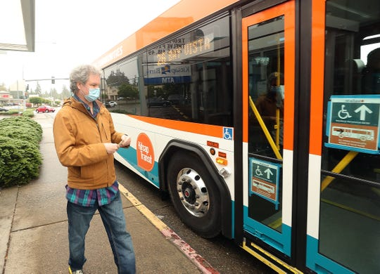 Dennis Harman prepares to board the bus at the Kitsap Transit Bus Stop in front of the R & H Market on Kitsap Way in Bremerton on May 26.