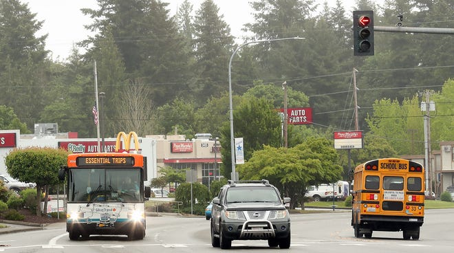 """FILE — """"Essential Trips"""" flashes across the reader board of a Kitsap Transit bus on Kitsap Way in Bremerton in May 2020. Federal COVID-19 relief funds and sales tax increases is allowing the phased return on Sunday bus service by Kitsap Transit."""