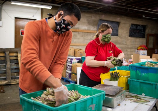 FILE - In this April 10, 2020 file photo, Missael Lopez, left, and Laura McIlrath Riel bundle asparagus at McIlrath Family Farm stand in Yakima during the coronavirus outbreak. The state of Washington is implementing safety recommendations to battle a large outbreak of the coronavirus in the agricultural area in the central part of the state.