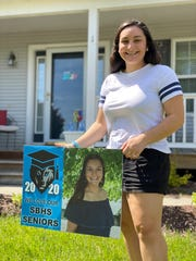 Mia Harton poses with her senior picture lawn sign delivered to her by her cap and gown-clad Assistant Principal. The South Burlington High School senior is being honored by her school in creative ways while she and her classmates finish up their final year of high school at home during the pandemic. May 21, 2020.