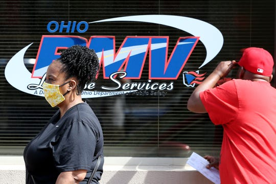 People wait in line for service, Tuesday, May 26, 2020, at the Bureau of Motor Vehicles office in downtown Cincinnati. The state is asking if those who go in-person to check in online beforehand at bmv.ohio.gov.