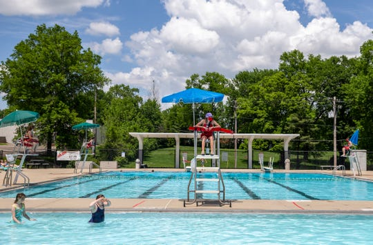 Lifeguard Christine Hoffmann watches swimmers at the Greenhills swimming pool Tuesday, May 26, 2020, the first day pools are allowed open in Ohio because of COVID-19. There will be three swim sessions per day, each session is limited to 98 people at the pool.