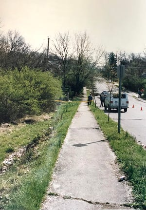 "Cincinnati police investigate a wooded lot in Avondale where the body of Sharman ""Marie"" Kinney was discovered April 13, 1992. Kinney, 40, had been strangled, suffocated and stabbed."