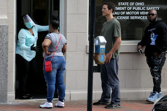 A Bureau of Motor Vehicles employee talks to a woman as people wait in line for service, Tuesday, May 26, 2020, at the Bureau of Motor Vehicles office in downtown Cincinnati. The state is asking if those who go in-person to check in online beforehand at bmv.ohio.gov.