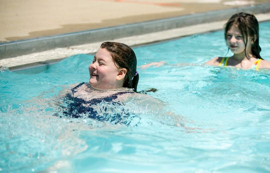 Alicia Bain, 9, left and her sister Ella Bain, 10 play at the Greenhills swimming pool Tuesday, May 26, 2020, the first day pools are allowed open in Ohio because of COVID-19. The girls' mother Joanna Bain of Greenhills said they normally have a season pass to the pool.