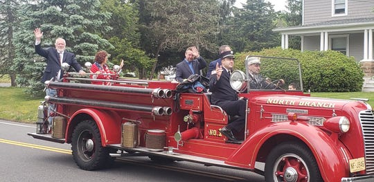 "Branchburg Mayor Tom Young waves from the back of a North Branch Volunteer Fire Company's fire engine during the Neshanic Fire Company's modified ""Wave By"" Memorial Day Parade on Monday."