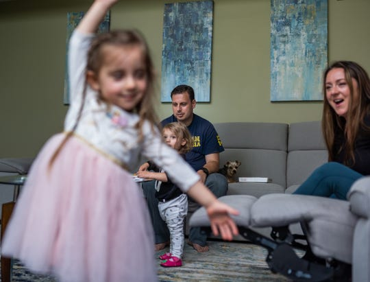 """Dr. Eugene Vovchuk sits with his wife Brooke and their daughters Madeline, left, and Abigail and their dog Rocky at their home on May 15 while recovering from COVID-19. """"It was a humbling experience to be on the other side,"""" said Vovchuk, an anesthesiologist and critical care physician. """"I was intubated and paralyzed. They were doing last ditch efforts on me to get me better."""""""