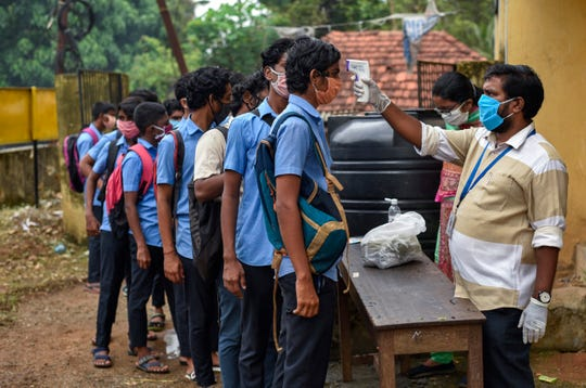 School children wearing masks line up to get their hands sanitized and temperatures checked as they arrive to appear for state board examination during the coronavirus pandemic in Kochi, Kerala state, India, Tuesday.