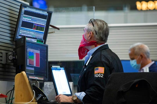 In this photo provided by the New York Stock Exchange, trader Eric Schumacher wears a bandana face mask as he works on the partially reopened trading floor, Tuesday, May 26, 2020, in New York.