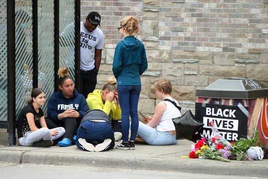 Mourners gather around a makeshift memorial, Tuesday, May 26, 2020 in Minneapolis, near where an black man was taken into police custody the day before who later died.