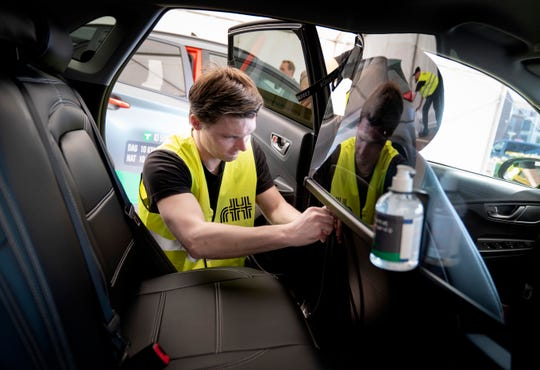 Danish taxi company Dantaxi installs safety measures in their vehicles, in Copenhagen, Tuesday.  The cars are fitted with information stickers, plexiglass segregating the driver from passenger and hand sanitising liquid to control the spread of the COVID-19 coronavirus.
