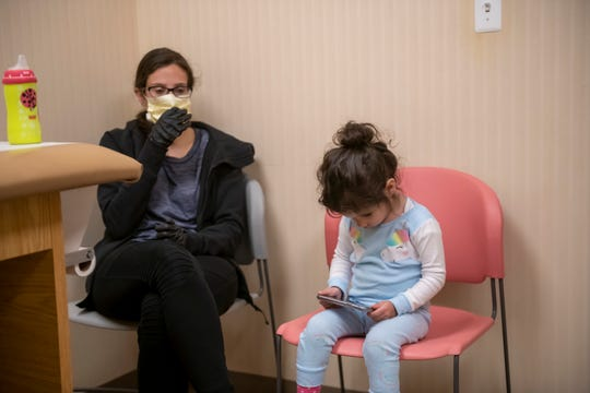 Two-year-old Khloe Sitto, from Farmington Hills, plays on the phone of her mother Karleen before receiving a hepatitis A vaccination at Beverly Hills Pediatrics, in Bingham Farms, May 26, 2020.