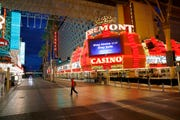 In this March 21, 2020, file photo, a man walks along a usually busy Fremont Street after casinos were ordered to shut down due to the coronavirus outbreak in Las Vegas. The coronavirus pandemic has been particularly brutal to the tourism-dependent economies of Nevada and Hawaii, lifting the unemployment rate in both states to about one-quarter of the workforce.