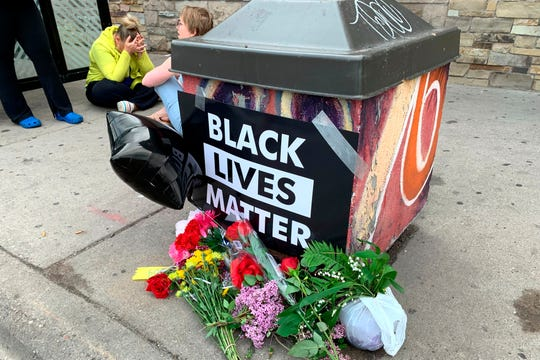 People gather around a makeshift memorial Tuesday, May 26, 2020, in Minneapolis. The FBI and Minnesota agents are investigating the death of a black man in Minneapolis police custody after video from a bystander showed a white officer kneeling on his neck during his arrest as he pleaded that he couldn't breathe.