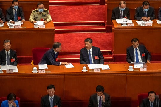 Chinese President Xi Jinping, center, talks to Wang Yang, center left,, Chairman of the Chinese People's Political Consultative Conference (CPPCC) during the second plenary session of China's National People's Congress (NPC) at the Great Hall of the People in Beijing, Monday, May 25, 2020.