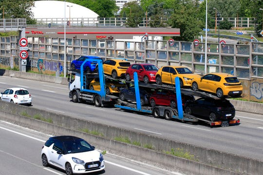 A truck carries new cars on the motorway leading to Paris, Tuesday, May 26, 2020 in Villacoublay, west of Paris.