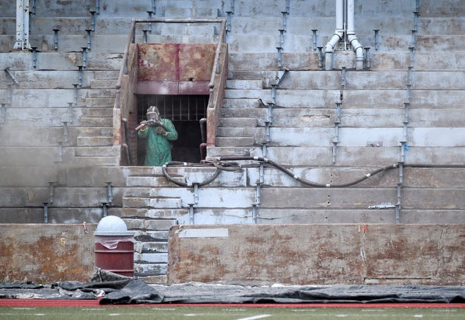 An employee of Tri-State Painting Co. Inc. sandblasts a section of Enlow Field on Tuesday morning. Three of the five public high school stadiums maintained by the EVSC, which also includes Reitz Bowl and Central Stadium, have begun repair work to the seating areas.