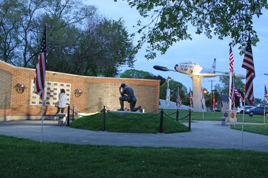 A person pauses at the Remembrance Wall at the Williams Park Veterans Memorial in Gibsonburg on Memorial Day.