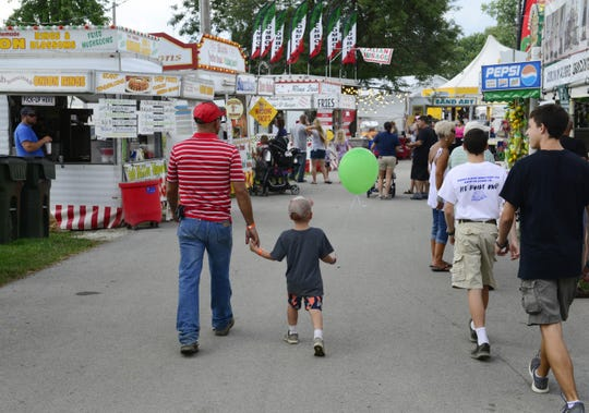 Visitors walk through the Sandusky County Fair on Tuesday, Aug. 21, 2018. The status of this year's county fair is uncertain, as the fair board waits for guidance from state officials on whether to hold the annual event.