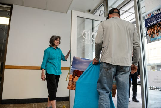 Local photographer Ross Mosher stopped by Gallery 16 on Tuesday afternoon to pick up several of his photographs exhibited there as Marcia Hocevar holds the door.  Galley 16 is closing down this week after 50 years in the Great Falls community.