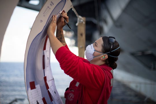 Navy Gunner's Mate 2nd Class Angela Haley, from Farmington, Minn., checks a target board after a small arms qualification aboard the aircraft carrier USS Theodore Roosevelt Sunday. Following an extended visit to Guam in the midst of the COVID-19 global pandemic, Theodore Roosevelt is underway conducting carrier qualifications.