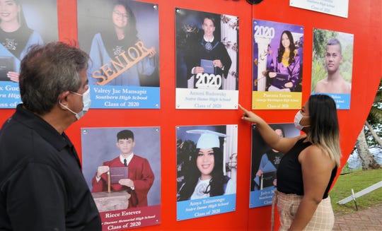 Steve Cruz and Alaessia Mansapit check out their handiwork on the Merizo tribute board to 2020  village high school graduates. Merizo, Guam, May 26, 2020.