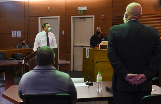 James L. Canto II, acting deputy attorney general for the Office of the Attorney General of Guam, top left, stands before Guam Police Department officer Steven Topasna, seated, and his attorney Tom Fischer, right, for a court hearing on the double pay lawsuit filed against GovGuam at the Superior Court of Guam in this May 26 file photo.